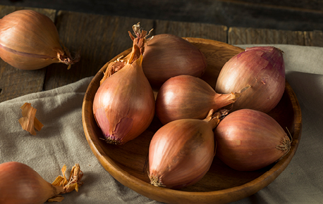 A shallot is a type of onion. Is it elongated and smaller than a regular onion, and has a golden or red, paper-like outer layer.