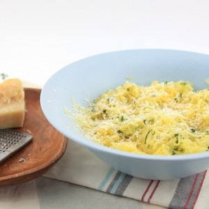 Spaghetti squash in a white bowl with herb butter and parm cheese