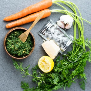 All the ingredients you need for carrot top pesto laid out on the table including parmesan  cheese, lemon, garlic.