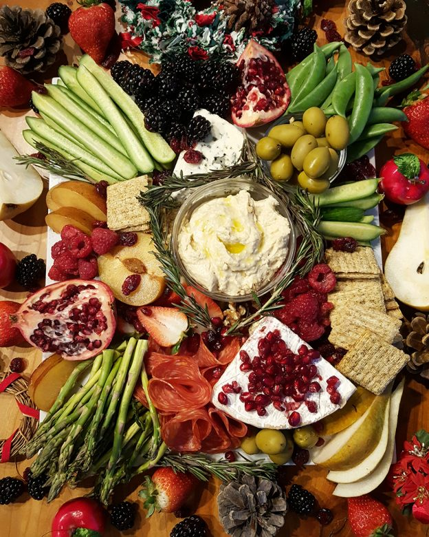 Grazing board filled with cheese, dip, fruits and veggies and breads