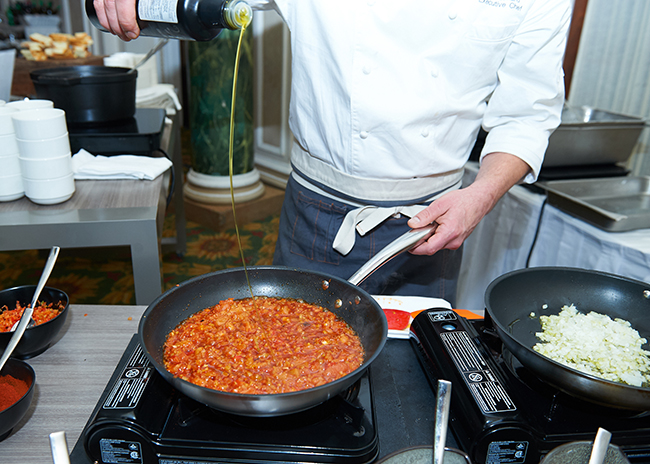 Chef Louis Simard adding olive oil to a simmering pot of veggies for his Egg Shakshuka