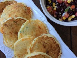 Dinner pancakes on a white plate with a side bowl of black bean salsa